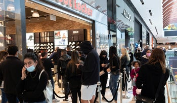 Shoppers wait in line to enter a store in Ramat Gan's Ayalon Mall, November 27, 2020.