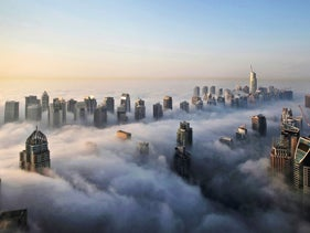 A thick blanket of early morning fog partially shrouds the skyscrapers of the Marina and Jumeirah Lake Towers districts of Dubai, United Arab Emirates.