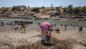 Tigray refugees who fled the conflict in the Ethiopia's Tigray arrive on the banks of the Tekeze River on the Sudan-Ethiopia border, in Hamdayet, eastern Sudan, November 21, 2020.