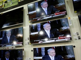A shop worker tries to fix a TV as Prime Minister Benjamin Netanyahu is seen on screen addressing the U.S. Congress in a shop in the city of Netivot, March 3, 2015.