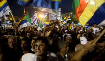 Protesters wave Druze and Israeli flags during a demonstration against Israel's Nation-State Law in Tel Aviv, August 4, 2018.