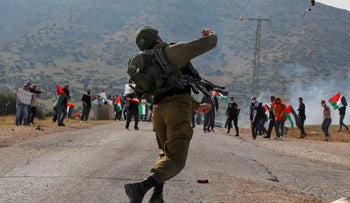 An Israeli soldier throws teargas against Palestinian protesters in the West Bank, November 24, 2020.