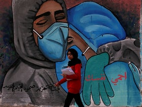 "A student walks past a mural which reads ""protect yourself"" in Arabic on the main road of Nusseirat refugee camp in central Gaza, November 24, 2020."
