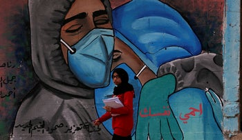 """A student walks past a mural which reads """"protect yourself"""" in Arabic on the main road of Nusseirat refugee camp in central Gaza, November 24, 2020."""