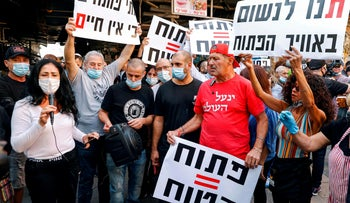 """Stall-owners at the Carmel Market in Tel Aviv, hold up signs reading """"Breathe"""" and """"Outdoors = Safe"""" as they demonstrate against government restrictions, November 17, 2020."""