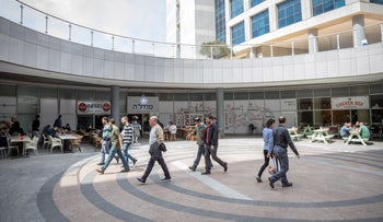 People walking during a workday in Herzliya Pituah, central Israel.