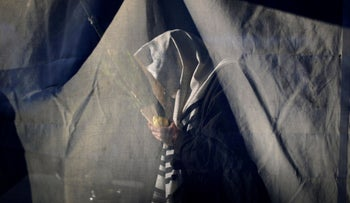 A man prays inside a tent as Orthodox Jews gather for outdoor Sukkot holiday prayers to avoid over-crowding at a synagogue following COVID-19 regulations. Monsey, NY, October 5, 2020