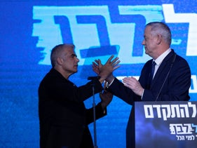 Yair Lapid (L) and Benny Gantz go to embrace on the March campaign trail, Tel Aviv, March 3, 2020.