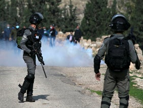 Palestinian demonstrators react from tear gas fired by Israeli forces during a protest against Israeli settlements in Kafr Malik in the West Bank, December 4, 2020.