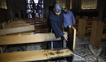 A priest checks a damaged pew after a man poured out flammable liquid inside the Church of All Nations in the Garden of Gethsemane, east Jerusalem, December 4, 2020.