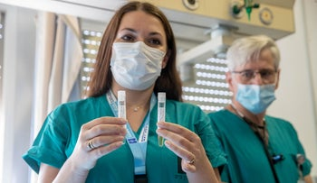 A health care worker holds up Israel's COVID-19 vaccine as its clinical trials begin at Hadassah University Hospital, Ein Karem in Jerusalem, November 1, 2020.