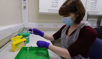 An NHS pharmacy technician simulates the preparation a coronavirus vaccine, during a staff training session ahead of the vaccine's rollout next week, at the Royal Free Hospital in London on December 4, 2020.