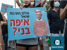 A protester holds a sign saying 'The cultural industries ask: Where's Benny?' referring to Kahol Lavan leader Benny Gantz, pictured wearing a Waldo outfit, Rosh Ha'ayin, August 9, 2020.