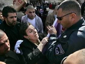Hanan Ashrawi scuffles with Israeli police officers as they take her election banner from her during a campaign stop in front of the Damascus Gate in Jerusalem's Old City, January 3, 2006