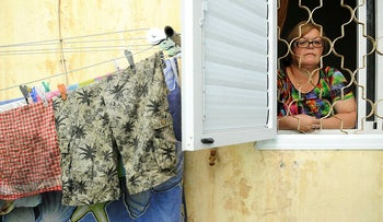 A woman living in poverty looks out her apartment window in Haifa, 2014.