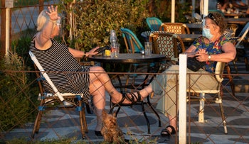 People sit outdoors at a restaurant in Jaffa, July 9, 2020.