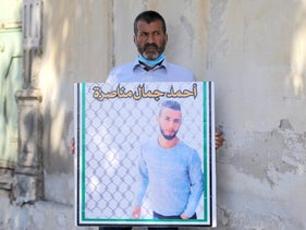 Ahmad Manasra's father, Jamal, holds up a poster of his son outside the military court in Jaffa, August 17, 2020.