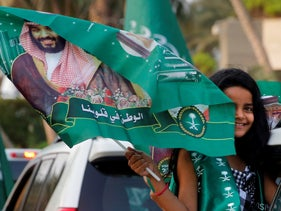 A Saudi girl waves a national flag with picture of Saudi Crown Prince Mohammed bin Salman during celebrations for National Day, commemorating the founding of the Kingdom of Saudi Arabia. Jiddah,  Sept. 23, 2020