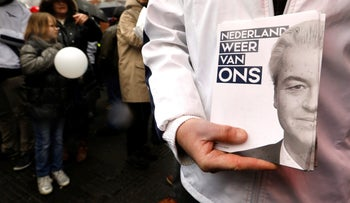 """A supporter of Dutch far-right politician Geert Wilders holding leaflets during Wilders' election campaign, March 2017. The slogan says """"The Netherlands belongs to us again."""""""