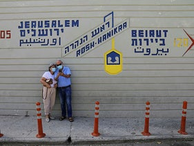 A couple wearing face masks, visit the Rosh Hanikra border crossing with Lebanon, in Rosh Hanikra, northern Israel October 13, 2020