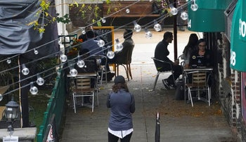 Customers sit outside a restaurant offering outdoor service, Thursday October, 22, 2020, in Kew Gardens in the Queens borough of New York.