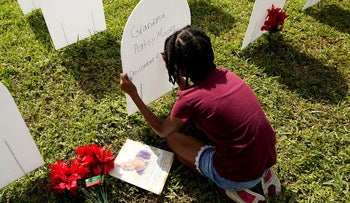 In this Nov. 24, 2020, file photo, Kyla Harris, 10, writes a tribute to her grandmother Patsy Gilreath Moore, who died at age 79 of COVID-19, at a symbolic cemetery created to remember and honor lives lost to COVID-19 in the Liberty City neighborhood of Miami