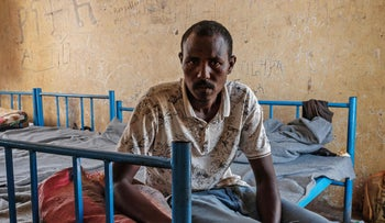 Kheder Adam, an Eritrean refugee who fled the Ethiopia's Tigray conflict, poses on his bed after a media interview at the Border Reception Center in Hamdayit, eastern Sudan, on December 8, 2020.