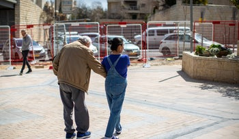 A caregiver walks with an elderly man in Jerusalem.
