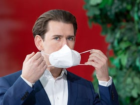 Austrian Chancellor Sebastian Kurz holds a face mask during a press conference at the Messe Wien fair grounds in Vienna, December 7, 2020.