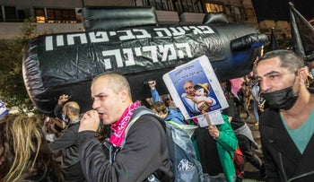Protesters holding up an inflatable submarine with the inscription 'Harming State Security' in Tel Aviv