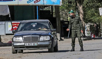 A Palestinian policeman checks cars during restricted movement on weekends due to rising COVID-19 infection in Rafah, Gaza Strip, December 11, 2020.