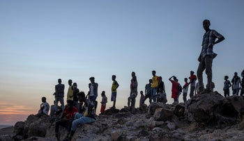 People who fled the conflict in Ethiopia's Tigray region, stand on a hill top over looking Umm Rakouba refugee camp in Qadarif, eastern Sudan, Thursday, November 26, 2020.