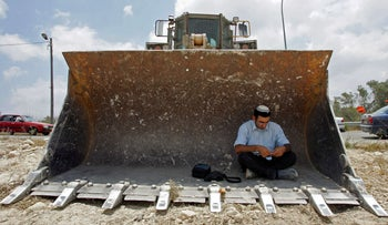 A Jewish settler prays in a bulldozer at the Homesh Jewish settlement in the northern West Bank July 6, 2005.