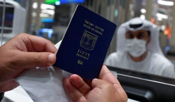 An Israeli man presents his passport for control upon arrival from Tel Aviv to the Dubai airport in the United Arab Emirates, on November 26, 2020