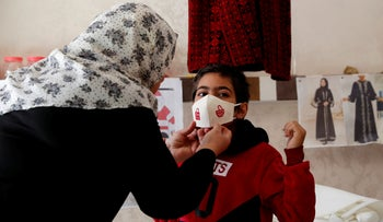 Suhad Saidam adjusts one of her face masks on a youth at her sewing workshop in Gaza City, December 14, 2020.