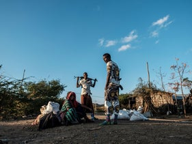 Men holding weapons stand next to a woman in the village of Bisober, in Ethiopia's Tigray region on December 9, 2020