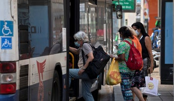 People board a bus in Tel Aviv, October 7, 2020.