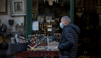 A man walks by a Judaica store in Jerusalem during Hanukkah, December 2020.