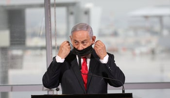 Israel's Prime Minister Benjamin Netanyahu removes his face mask before giving a speech at a ceremony to celebrate the first commercial flight from Dubai to Israel, Novemner 26, 2020.
