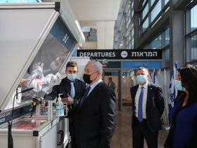 Israel's Prime Minister Benjamin Netanyahu, center, stands in front of a coronavirus testing booth at Ben Gurion Airport, December 2020.