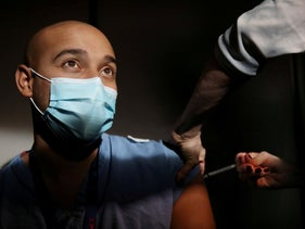 A doctor receives a Pfizer coronavirus vaccine at Massachussetts General Hospital in Boston, December 16, 2020.