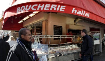 A man walks past a butcher shop in Paris which prominently advertises that it sells halal meat, 2012.