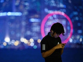 File photo: A man uses his mobile phone while standing on a promenade that runs along Victoria Harbor in Hong Kong on December 14, 2020.