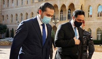 Lebanon's Prime Minister-designate Saad al-Hariri walks with Lebanon's caretaker Prime Minister Hassan Diab at the government palace in Beirut, Lebanon, December 11, 2020.