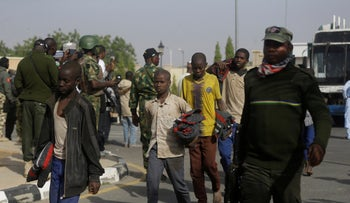 A group of schoolboys are escorted by Nigerian military and officials following their release after they were kidnapped last week, Friday December 18, 2020 in Katsina, Nigeria.