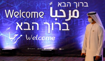 An Emirati man looks walks past a sign welcoming guests to a signing ceremony between the UAE and Israeli football associations. Dubai, December 14, 2020.