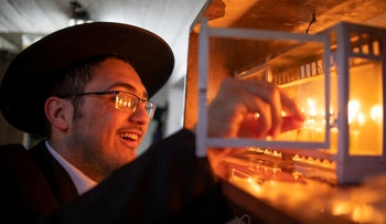 An ultra-Orthodox Jewish man lights candles to mark Hanukkah, the 8-day Jewish Festival of Lights, amid the coronavirus disease (COVID-19) restrictions, in Ashdod, Israel December 2020.