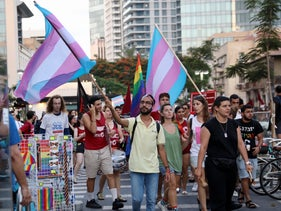 People wave transgender pride flags as they march in Tel Aviv, July 2019.