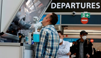 A medic collects a swab sample from a traveler at the COVID-19 coronavirus rapid testing center in Ben Gurion International Airport in Lod, December 2, 2020