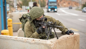 File photo: A soldier guarding a bus stop in the West Bank.